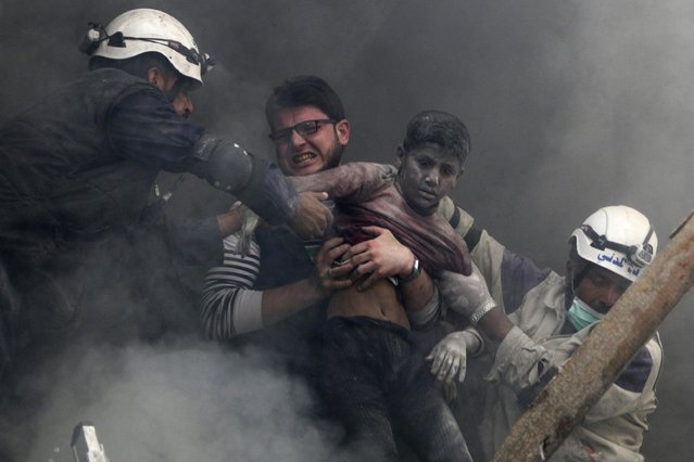 Men rescue a boy from under the rubble after what activists said were explosive barrels were dropped by forces loyal to Syria's President Bashar Al-Assad in the Al-Shaar neighbourhood of Aleppo, in this April 6, 2014 file photo. (Photo by Hosam Katan/Reuters)