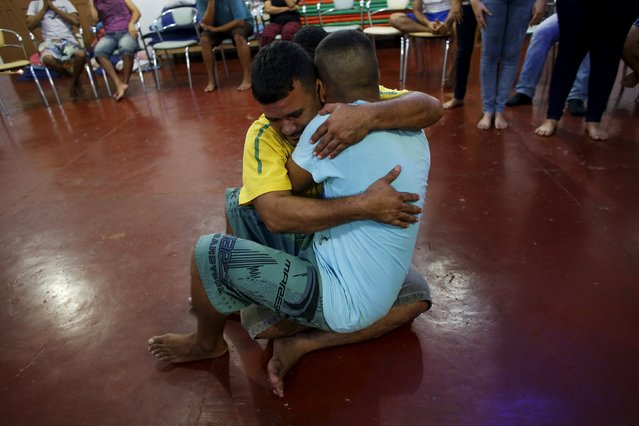 Prisoners Sergio Luiz Brito Aponte (L), 38, and Alexandre Valente, 31, embrace while taking part in a Family Constellations therapy session as part of the ACUDA programme, at a complex of ten prisons in Porto Velho, Rondonia State, Brazil August 27, 2015. (Photo by Nacho Doce/Reuters)