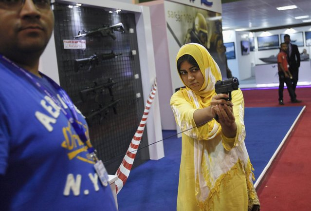 A visitor aims a gun at an exhibit during the International Defence Exhibition and Seminar (IDEAS 2014) in Karachi December 3, 2014. At least 88 delegations from 47 countries took part at the 8th biennial IDEAS 2014 at the Karachi Expo Centre, local media reported. (Photo by Akhtar Soomro/Reuters)
