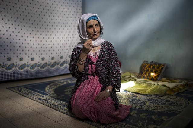 Aisha Djelal, 73, a berber woman from the Chaouia region, who has facial tattoos, gestures as she sits inside her house in Babar, Algeria October 10, 2015. Djelal was tattooed when she was 25. She wanted to be more attractive than other girls her age. Among the Chaouia people of the Aures mountains, a woman's beauty used to be judged by her tattoos. Traditionally, the more a woman was tattooed the higher she was prized by local men. (Photo by Zohra Bensemra/Reuters)