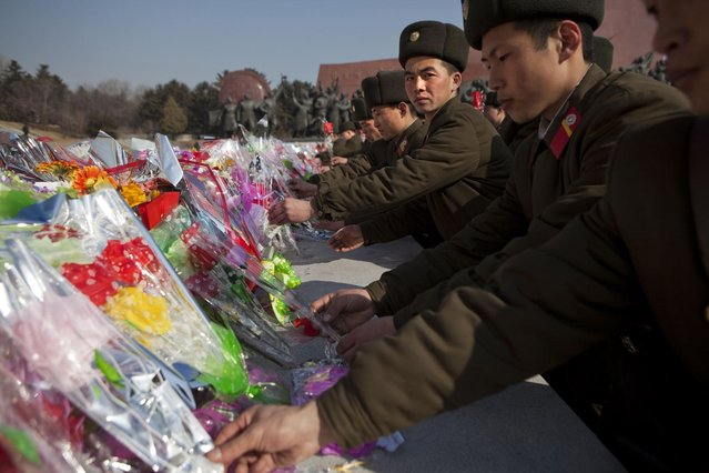 North Korean soldiers lay flowers at the base of bronze statues of the late leaders Kim Il Sung and Kim Jong Il to pay their respects in Pyongyang, North Korea on Saturday, February 16, 2013. North Koreans turned out to commemorate what would have been the 71th birthday of Kim Jong Il who died on December 17, 2011. (Photo by David Guttenfelder/AP Photo)