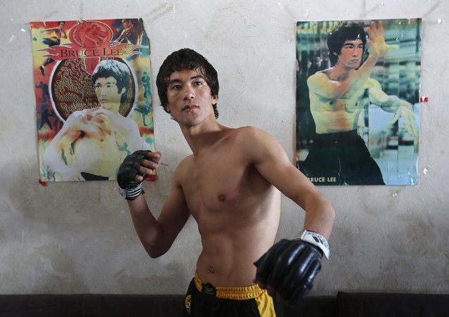 Abbas Alizada, who calls himself the Afghan Bruce Lee, poses for a picture in front of Bruce Lee posters after exercising in Kabul December 9, 2014. (Photo by Mohammad Ismail/Reuters)
