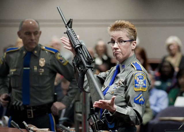 Firearms Training Unit Detective Barbara J. Mattson of the Connecticut State Police holds up a Bushmaster AR-15 rifle, the same make and model of gun used by Adam Lanza in the Sandy Hook School shooting, for a demonstration during a hearing of a legislative subcommittee reviewing gun laws, at the Legislative Office Building in Hartford, Conn., Monday, January 28, 2013. The parents of children killed in the Newtown school shooting called for better enforcement of gun laws Monday at the legislative hearing. (Photo by Jessica Hill/AP Photo)