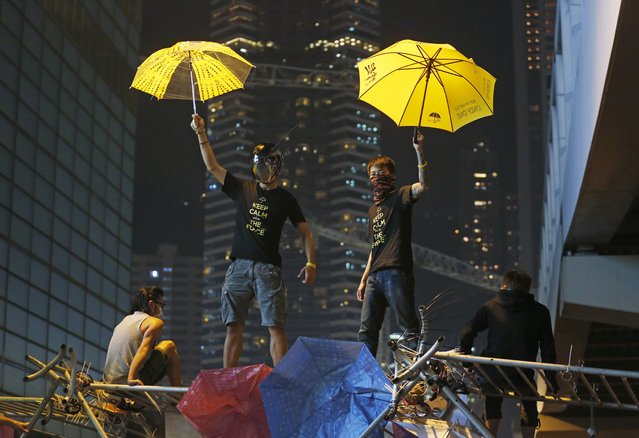 Protesters pose for photographs on a barricade at the occupied area outside government headquarters in Hong Kong Wednesday, December 10, 2014. Hong Kong's dwindling number of pro-democracy protesters vowed Wednesday to stay until the last minute before authorities clear them off a highway where they've been camped out for more than two months. (Photo by Kin Cheung/AP Photo)