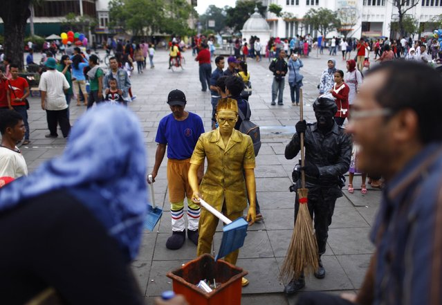 Visitors laugh as statue street performers pose as cleaning workers at Fatahilah museum park in Jakarta's old city April 14, 2013. As many as 10 statue performers gather at Fatahilah museum park on weekends to entertain visitors. (Photo by Reuters/Beawiharta)