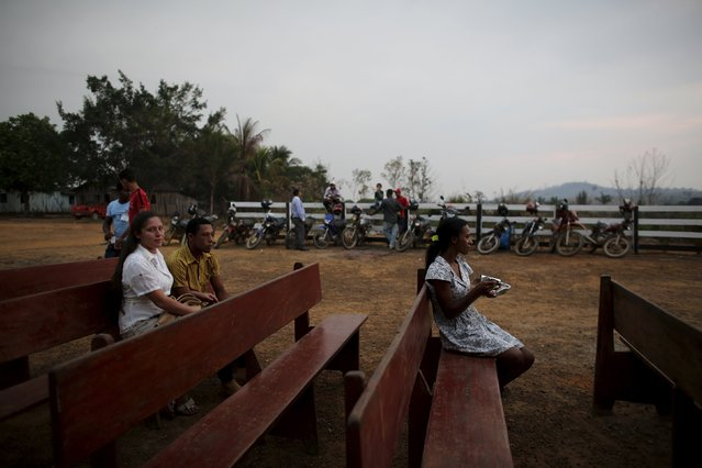 Residents sit before a mass is held in an evangelical church in the village of Rio Pardo next to Bom Futuro National Forest, in the district of Porto Velho, Rondonia State, Brazil, August 29, 2015. (Photo by Nacho Doce/Reuters)