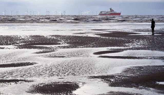 "Polar research ship, the RRS Sir David Attenborough, sails out of the River Mersey past Antony Gormley's art installation ""Another Place"" at Crosby, north west England on November 03, 2020. In November, the shipyard will formally hand over the ship to the Natural Environment Research Council (NERC). Early next year the ship will undertake ice trials in the Arctic, and in November 2021 make its maiden voyage to Antarctica. (Photo by Paul Ellis/AFP Photo)"