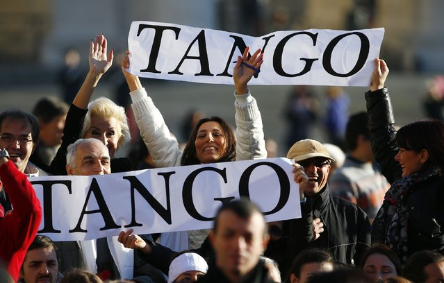 Tango dancers hold banners for Pope Francis, who's 78th birthday is today, as he arrives to lead his general audience at the Vatican, December 17, 2014. (Photo by Tony Gentile/Reuters)