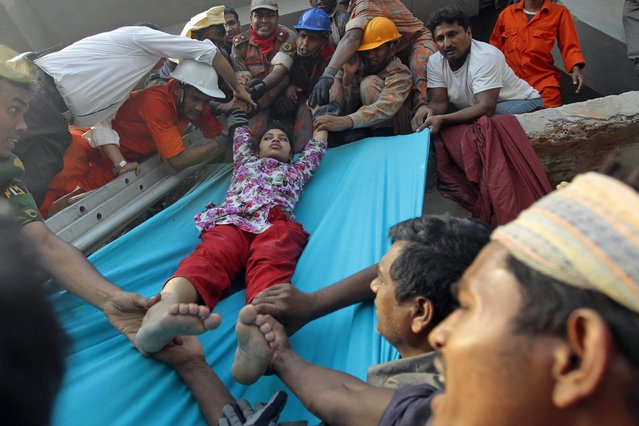 Rescuers lower down a survivor from the debris of a building that collapsed in Savar, near Dhaka, Bangladesh, Wednesday, April 24, 2013. An eight-storey building housing several garment factories collapsed near Bangladesh's capital on Wednesday, killing dozens of people and trapping many more under a jumbled mess of concrete. Rescuers tried to cut through the debris with earthmovers, drilling machines and their bare hands. (Photo by A. M. Ahad/AP Photo)
