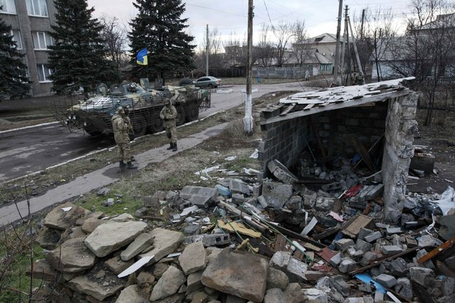 Ukrainian servicemen stand near a building damaged during fighting between pro-Russian rebels and Ukrainian government forces in the eastern Ukrainian town of Debaltseve in Donetsk region, December 24, 2014. (Photo by Valentyn Ogirenko/Reuters)