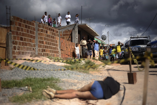 Residents observe the body of a person shot in the head in the Sao Cristovao slum of Salvador, Bahia State, April 13, 2013. One of Brazil's main tourist destinations and a 2014 World Cup host city, Salvador suffers from an unprecedented wave of violence with an increase of over 250% in the murder rate, according to the Brazilian Center for Latin American Studies (CEBELA). (Photo by Lunae Parracho/Reuters)