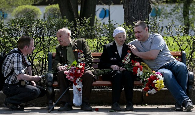 Two young men speak with WW II veterans Aleksakin Nikolay 90, second left, and Anna Parukhova, 90, second right, during Victory Day in Moscow's Gorky Park. (Photo by Mikhail Metzel/Associated Press)