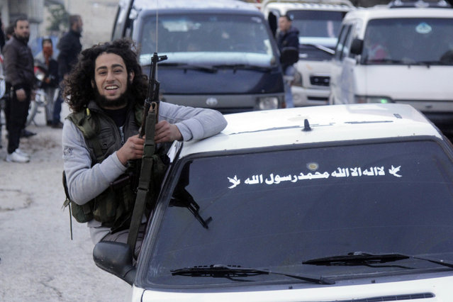 A Free Syrian Army fighter sits on a car celebrating a fellow fighter's wedding in Jabal al-Akrad area in Syria's northwestern Latakia province, December 11, 2014. (Photo by Alaa Khweled/Reuters)