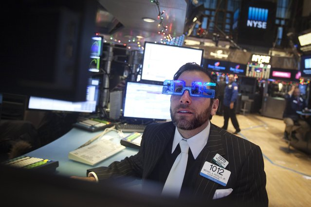 Trader Michael Pistillo works on the floor of the New York Stock Exchange while wearing 2015 novelty glasses on New Year's Eve, the last trading day of the year, in New York December 31, 2014. (Photo by Carlo Allegri/Reuters)