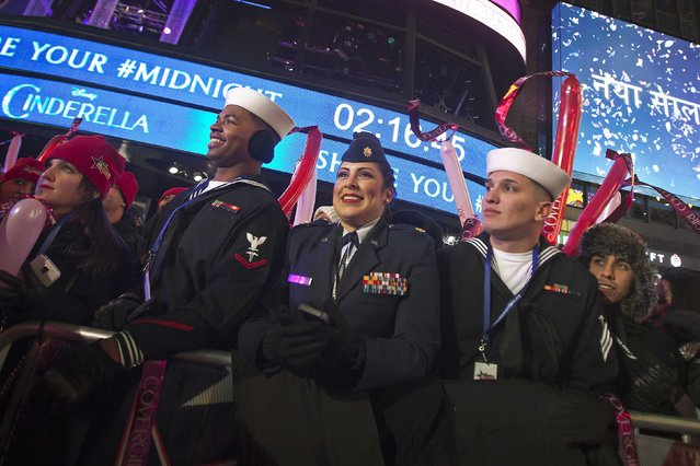 Members of the United States Navy watch the festivities in Times Square on New Year's Eve in New York December 31, 2014. (Photo by Carlo Allegri/Reuters)