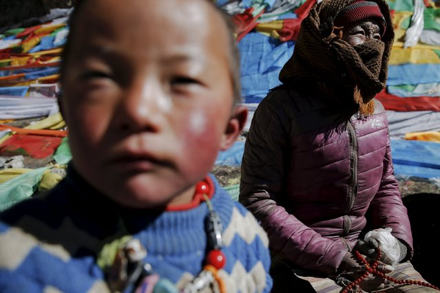 A Tibetan woman and boy sit in front of a rock decorated with prayer flags at Namtso lake in the Tibet Autonomous Region, China November 18, 2015. (Photo by Damir Sagolj/Reuters)