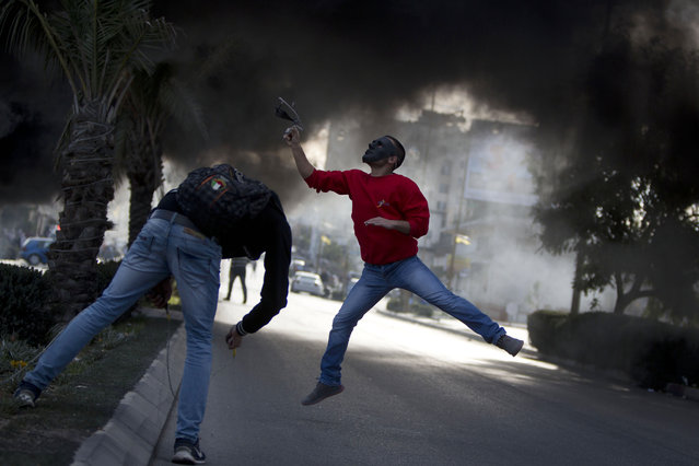 A Palestinian protester uses a sling shot to hurl stones at Israeli troops during clashes, in the West Bank city of Ramallah, Friday, November 20, 2015. (Photo by Majdi Mohammed/AP Photo)