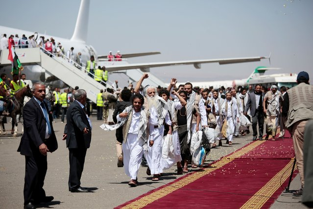 Yemeni prisoners chant slogans during their arrival after being released by the Saudi-led coalition at the airport in Sanaa, Yemen, Friday, October 16, 2020. Yemen's warring sides completed a major, U.N.-brokered prisoner swap on Friday, officials said, a development that could revive the country's stalled peace process after more than five years of grinding conflict. (Photo by Hani Mohammed/AP Photo)