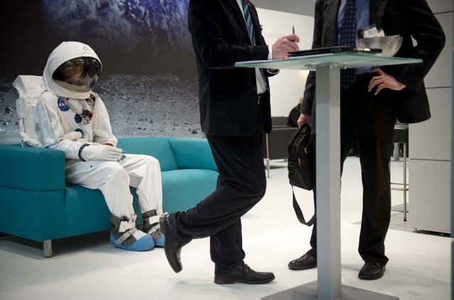 An astronaut is seen sitting on the couch behind two business men at the Wittenstein booth at the Hanover industrial fair on April 8, 2013 in Hanover, central Germany. (Photo by Odd Andersen/AFP Photo)