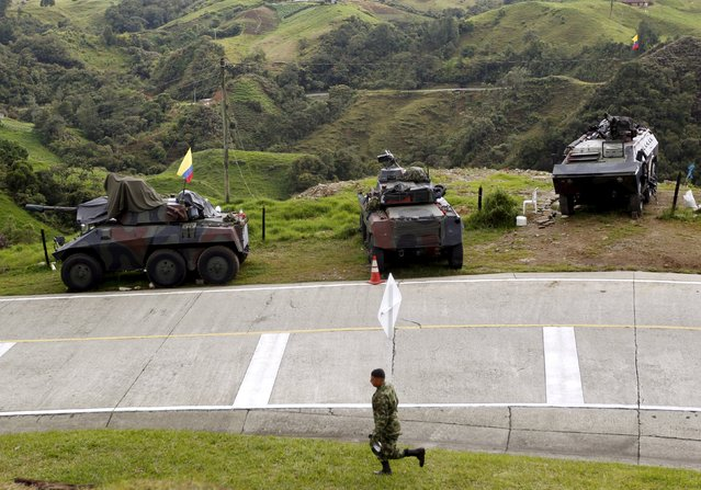 Armored army vehicles are seen on guard along a road close to a zone of landmines planted by rebels groups near Sonson in Antioquia province, November 19, 2015. (Photo by Fredy Builes/Reuters)