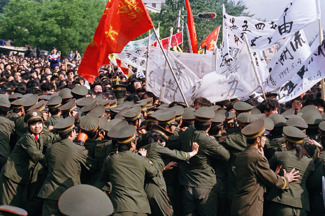 Chinese police try in vain to contain a huge crowd of student marchers during a pro-reform demonstration on Thursday, May 4, 1989 in Beijing. (Photo by Sadayuki Mikami/AP Photo)