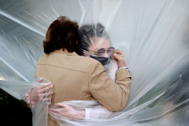Olivia Grant (R) hugs her grandmother, Mary Grace Sileo through a plastic drop cloth hung up on a homemade clothes line during Memorial Day Weekend on May 24, 2020 in Wantagh, New York. It is the first time they have had contact of any kind since the coronavirus COVID-19 pandemic lockdown started in late February. (Photo by Al Bello/Getty Images)