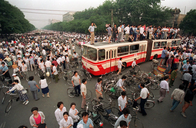 A huge crowd gathers at a Beijing intersection where residents used a bus as a roadblock to keep troops from advancing toward Tiananmen Square in this June 3, 1989 photo. (Photo by Jeff Widener/AP Photo)