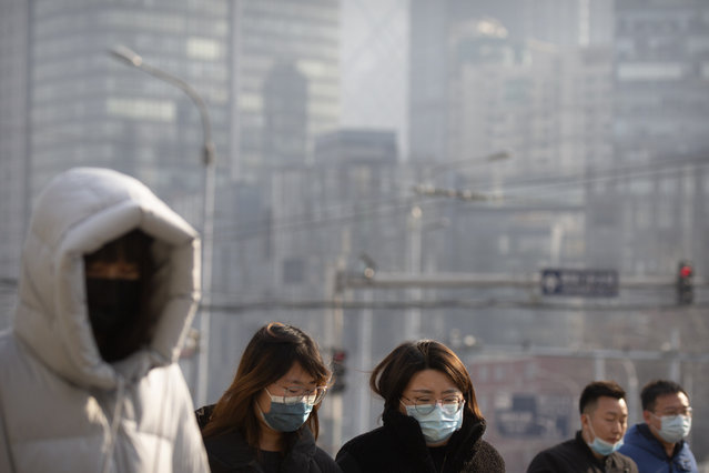 People wearing face masks to protect against the spread of the coronavirus walk across an intersection in Beijing, Wednesday, January 20, 2021. China is now dealing with coronavirus outbreaks across its frigid northeast, prompting additional lockdowns and travel bans. (Photo by Mark Schiefelbein/AP Photo)