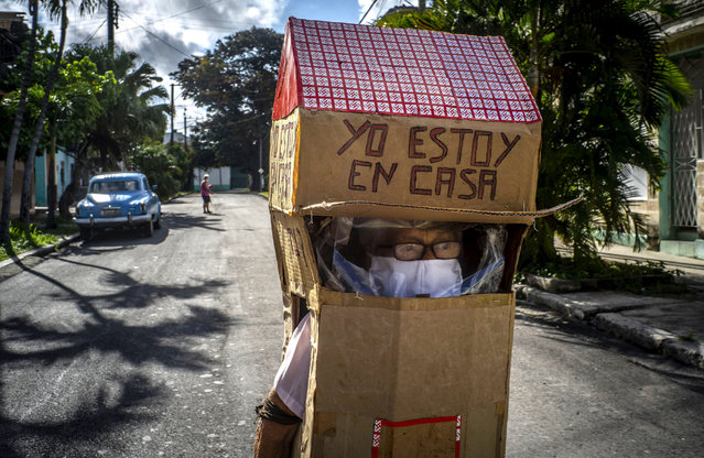 """Feridia Rojas, a retired nurse, wears a cardboard box as a protective measure against the spread of the new coronavirus, in Havana, Cuba, Wednesday, July 8, 2020. The 82-year-old pensioner shuffles through the streets of Havana on shopping excursions wearing the cardboard box with a handwritten message that reads in Spanish, """"I'm home"""". (Photo by Ramon Espinosa/AP Photo)"""
