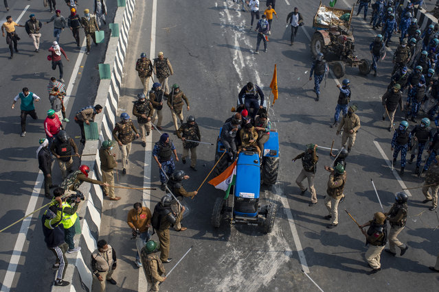 Indian policemen beat farmers driving a tractor after protesting farmers and policemen clash during India's Republic Day celebrations in New Delhi, India, Tuesday, January 26, 2021. (Photo by Altaf Qadri/AP Photo)