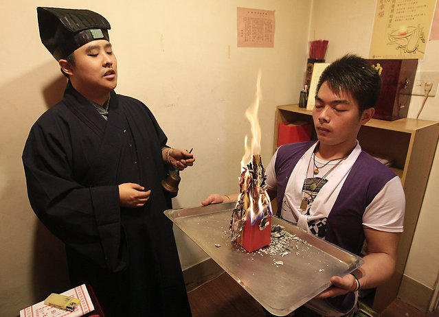 Lu Wei-ming (L), priest of the Wei-ming temple, and a worshipper burn a Taoist paper amulet during a prayer ritual at the temple in New Taipei city January 8, 2015. The shrine, down a narrow alleyway in a bustling district of the city, is dedicated to a deity who has watched over homosexuals for four centuries. (Photo by Pichi Chuang/Reuters)