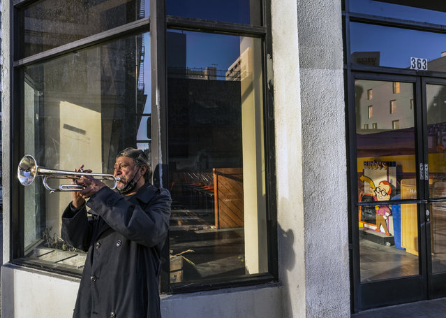 "Street musician Roberto Hernandez, originally from El Salvador, plays ""Lambada"" on his trumpet outside Buddy's, a restaurant temporarily closed due to the COVID-19 pandemic, in downtown Los Angeles on Friday, February 5, 2021. (Photo by Damian Dovarganes/AP Photo)"