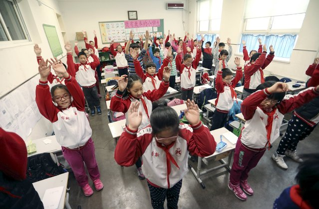 Primary school students exercise inside a classroom as outdoor activities are banned due to heavy smog, in Beijing, China, December 7, 2015. (Photo by Reuters/Stringer)