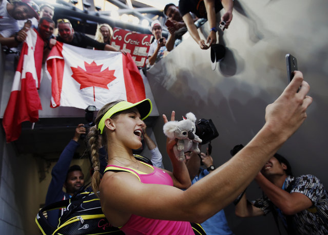 """Eugenie Bouchard of Canada takes a """"selfie"""" using a spectator's phone after defeating Kiki Bertens of the Netherlands during their women's singles second round match at the Australian Open 2015 tennis tournament in Melbourne January 21, 2015. (Photo by Issei Kato/Reuters)"""