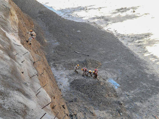 This photograph provided by Indo Tibetan Border Police (ITBP) shows ITBP personnel begin rescue work after a portion of Nanda Devi glacier broke off in Tapovan area of the northern state of Uttarakhand sending a massive flood of water, mud and debris into areas below, India, Sunday, February 7, 2021. (Photo by Indo Tibetan Border Police via AP Photo)