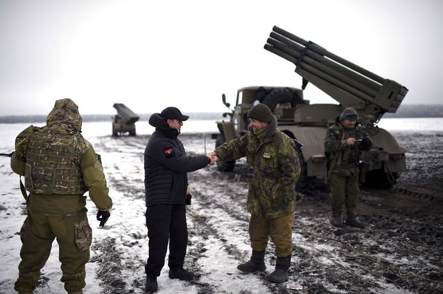 In this Sunday, January 25, 2015 pool photo, Ukrainian parliament lawmaker and leader of Ukraine's Radical Party Oleh Lyashko, second left, greets Ukrainian soldiers while visiting their position near the town of Volnovakha, in eastern Ukraine. (Photo by Osman Karimov/AP Photo)