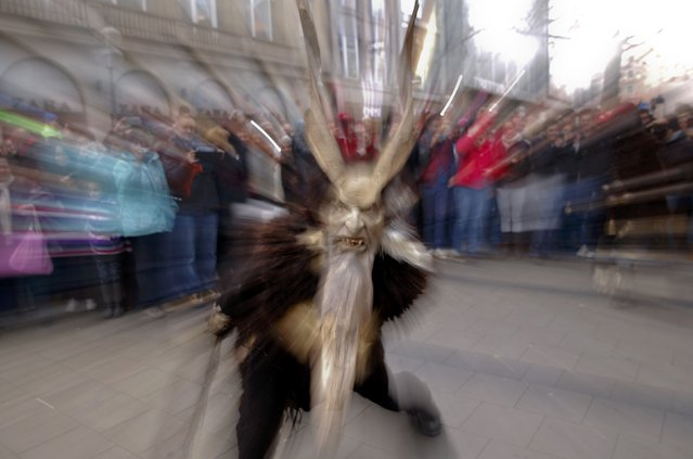 A man dressed as a 'Krampuss' parades at Munich's Christmas market, December 13, 2015. Young single men will wear the traditional attires known as 'Krampusse', consisting of animal skins and masks, with large cow-bells to make loud and frightening noises and parade through the city. They follow 'Saint Nicholas' from house to house in December each year to bring luck to the good and punish the idle. (Photo by Michael Dalder/Reuters)