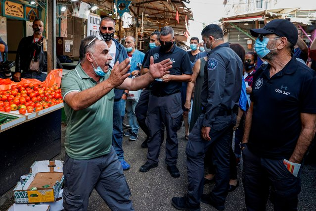 A stall-owner (mask-clad due to COVID-19 coronairus pandemic) at the Shuk HaCarmel (Carmel Market) in Israel's Mediterranean coastal city of Tel Aviv, protests before officials of the Tel Aviv-Yafo municipality for being fined for illegally reopening on November 17, 2020, amidst a health ordinance banning businesses from reopening. Several shopkeepers opened their stalls in violation of health regulations, one of which was immediately fined by Tel Aviv municipality inspectors. The trader said he did not intend to pay the 5000 shekel fine (approximately 1485 US dollars) and would appeal to court. (Photo by Jack Guez/AFP)