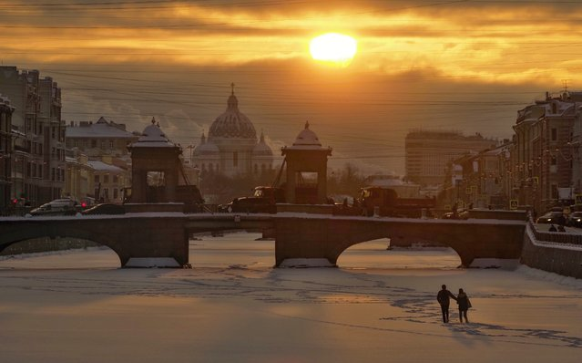 A couple walk on the ice on the frozen Fontanka River at sunset in St. Petersburg, Russia, Thursday, February 4, 2021, with Troitsky (Trinity) Cathedral in the background. The temperature in St. Petersburg dropped to minus 12 degrees Centigrade (10 degrees Fahrenheit). (Photo by Dmitri Lovetsky/AP Photo)