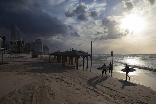 Surfers carry their boards along the beach front during a nationwide lockdown to curb the spread of the oronavirus, In Tel Aviv, Israel, Sunday, January 17, 2021. (Photo by Oded Balilty/AP Photo)