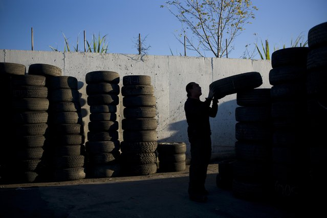 In this Thursday, November 19, 2015 photo, junkyard employee Fabio Flores stacks up used tires at Aadlen Brothers Auto Wrecking, also known as U Pick Parts, in the Sun Valley section of Los Angeles. (Photo by Jae C. Hong/AP Photo)
