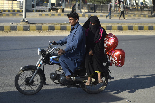 A woman carries a heart shaped balloon while sitting with her husband on a motorbike during Valentine's day, in Karachi on February 14, 2021. (Photo by Rizwan Tabassum/AFP Photo)