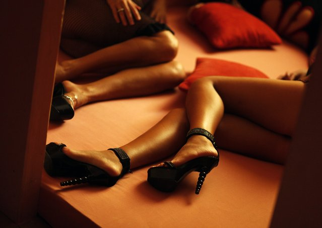 """Romanian prostitutes pose in the brothel """"p*ssy Club"""" in Schoenefeld in this April 15, 2009 file photo. A jump in the Swiss franc against the euro, which threatens to push the country's economy into recession, is boosting trade in brothels across the border in Germany. (Photo by Hannibal Hanschke/Reuters)"""
