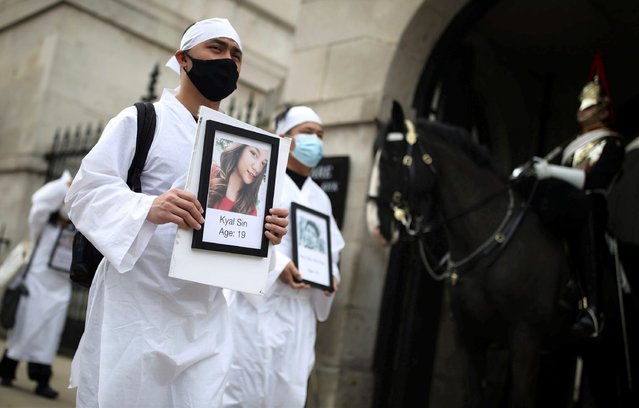 Protesters holding photos of protestors killed, as they march in Westminster, demonstrating against the Feb. 1 coup in Myanmar which ousted Aung San Suu Kyi's elected government, in London, Wednesday, March 31, 2021. (Photo by Aaron Chown/PA Wire via AP Photo)