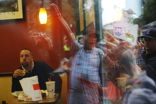 A man eats in a Burger King restaurant while demonstrators gather outside in Boston, Massachusetts August 29, 2013, part of a nation-wide fast food workers strike asking for $15 per hour wages and the right to form unions. (Photo by Brian Snyder/Reuters)