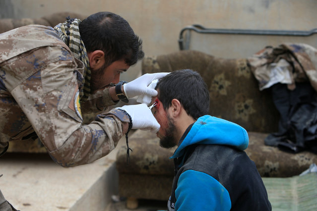 A member of the Iraqi security forces provides medical treatment for an injured man, during a battle with Islamic State militants in Mosul, Iraq, November 30, 2016. (Photo by Alaa Al-Marjani/Reuters)