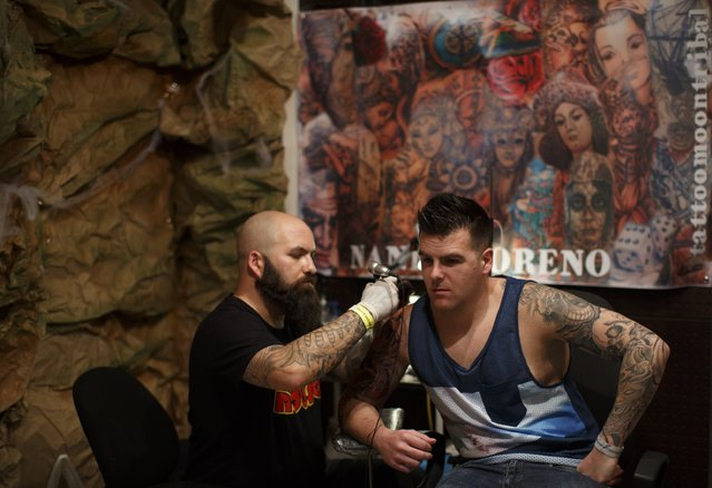Tattooist Nandi Moreno (L) tattoos a customer during a tattoo convention in the Andalusian capital of Seville February 14, 2015. (Photo by Marcelo del Pozo/Reuters)