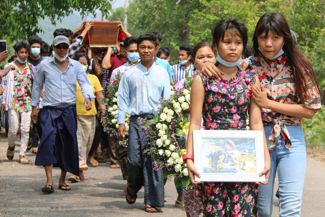 This handout photo taken and released by Dawei Watch on April 1, 2021 shows a relative leading the funeral procession for Kyaw Min Latt, also known as Poe Toe, after he was shot by security forces from a vehicle while he was riding past on his motorcycle on March 27 as the country remains in turmoil following the February military coup, in Dawei. (Photo by Dawei Watch/Handout via AFP Photo)