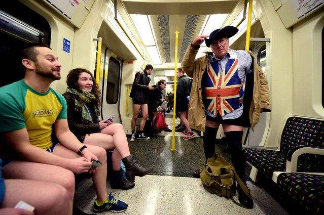 """articipants in the annual International """"No Pants Subway Ride"""" travel on a London underground train in London, on January 10, 2016. Started in 2002 with only seven participants, the day is now marked in over 60 cities around the world. The idea behind """"No Pants"""" is that random passengers board a subway car at separate stops in the middle of winter, without wearing trousers. The participants wear all of the usual winter clothing on their top half such as hats, scarves and gloves and do not acknowledge each other's similar state of undress. (Photo by Leon Neal/AFP Photo)"""