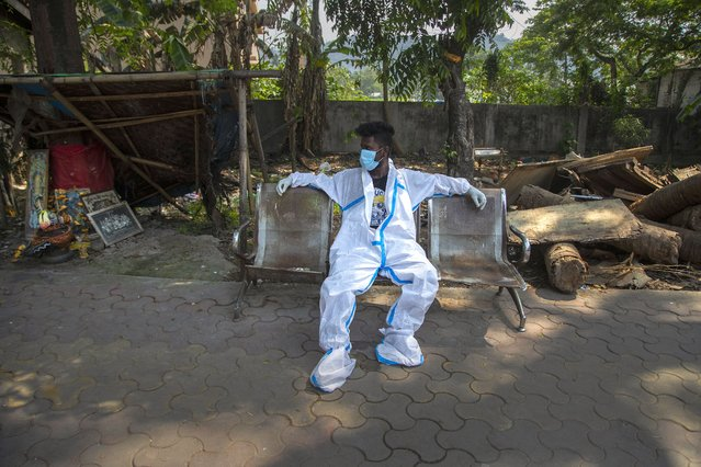 An exhausted health worker in protective suit takes rest after carrying a body of a person for cremation in Gauhati, India, Tuesday, April 27, 2021. Coronavirus cases in India are surging faster than anywhere else in the world. (Photo by Anupam Nath/AP Photo)